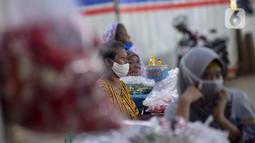 Pedagang kembang untuk berziarah menunggu pembeli di kawasan Gembrong, Prumpung, Jakarta, Kamis (23/4/2020). Jelang Ramadan, pedagang kembang untuk berziarah mengeluhkan sepinya pembeli karena adanya Pembatasan Sosial Berskala Besar (PSBB) untuk mencegah penyebaran COVID-19. (merdeka.com/Imam Buhori