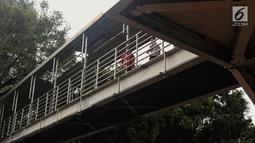 Atap yang rusak di JPO Medan Merdeka Barat, Jakarta, Jumat (19/1). Kondisi JPO yang penuh dengan genangan air dan atap yang rusak ini mengurangi kenyamanan bagi para pejalan kaki yang menggunakannya. (Liputan6.com/Johan Tallo)