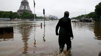 Seorang pria melewati jalan-jalan yang terendam banjir di pusat kota Paris. (pinterest.com)