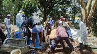 Proses pemakaman seorang warga Kota Malang diduga suspect corona Covid-19 di Kota Malang. Masyarakat diimbau tak menolak jenazah karena proses pemakaman sudah sesuai protokol (Humas Pemkot/Liputan6.com/Zainul Arifin)