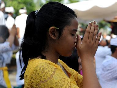 Umat Hindu berdoa saat perayaan Kuningan di sebuah pura di Pulau Serangan, Denpasar, Bali, Sabtu (20/2). Kuningan merupakan hari terakhir perayaan Galungan diyakini menjadi hari kekuasaan roh suci leluhur kembali ke langit. (AFP PHOTO/SONNY Tumbelaka)