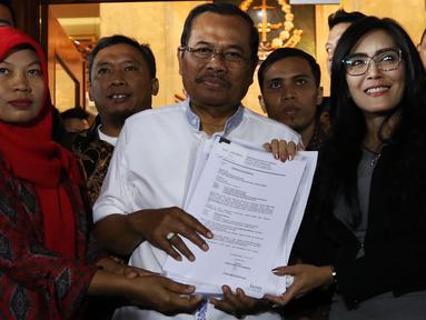 Jaksa Agung HM Prasetyo (tengah) menerima surat jaminan penangguhan eksekusi terhadap terpidana kasus pelanggaran UU ITE, Baiq Nuril Maknun(kiri)  dari anggota DPR Fraksi PDIP Rieke Diah Pitaloka di gedung Kejaksaan Agung, Jakarta, Jumat (12/7/2019). (Liputan6.com/Johan Tallo)