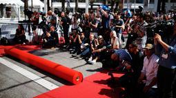 Fotografer menunggu pemasangan karpet merah di depan pintu masuk utama jelang upacara pembukaan Festival Film Cannes 2019 di Cannes, Prancis, Selasa (14/5/2019). Festival Film Cannes tahun ini memasuki gelaran ke-72. (REUTERS/Stephane Mahe)