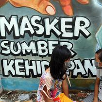Anak-anak berbincang di depan mural bertema COVID-19 di kawasan Tanah Tinggi, Tangerang, Banten, Rabu (20/1/2020). Kegiatan ini dalam rangka mensosialisasikan bahaya penyebaran COVID-19 kepada warga pengguna jalan umum. (merdeka.com/Arie Basuki)
