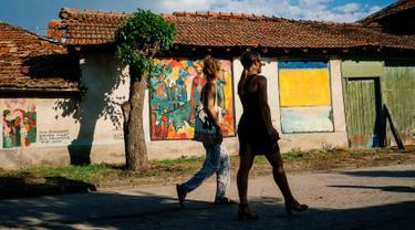 Dua orang wanita melewati lukisan mural karya seniman terkenal di dinding rumah desa Staro Zhelezare di Bulgaria, 4 Agustus 2018. Dengan populasi penduduk dibawah 500 orang, desa ini disulap menjadi galeri seni yang penuh mural. (AFP/Dimitar DILKOFF)