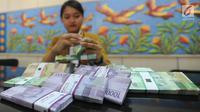 Teller menghitung uang pecahan kecil di kantor cabang Bank BJB di Melawai, Jakarta (7/6). Mengantisipasi kebutuhan dana masyarakat di bulan Ramadan dan Lebaran, pemerintah telah mengalokasikan uang tunai sebesar Rp 188,2 Triliun. (Merdeka.com/Arie Basuki)