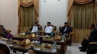 Menteri Kesehatan Republik Indonesia Terawan Agus Putranto diberikan hadiah berupa baju koko berwarna putih dan peci hitam saat mengunjungi Pondok Pesantren yang ada di Gontor. (Liputan6.com/Giovani Dio Prasasti)