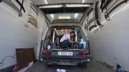 Seorang tukang las mengubah van menjadi food truck di sebuah bengkel di kota Ramallah, Tepi Barat, Selasa, 22 September 2020. Dengan sebagian besar restoran tutup karena pembatasan COVID-19, food truck memungkinkan pengusaha Palestina untuk menemukan cara tetap bekerja. (AP Photo/Nasser Nasser)
