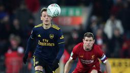 Gelandang Arsenal, Mesut Ozil berebut bola dengan gelandang Liverpool James Milner pada laga babak 16 Besar Carabao Cup di Anfield Stadium, Rabu (30/10/2019). Berimbang 5-5 di waktu normal, Liverpool menang 5-4 dalam adu penalti dan maju ke perempatfinal . (AP/Jon Super)