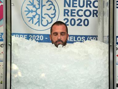 Pria Prancis, Romain Vandendorpe menutup matanya saat mencoba memecahkan rekor dunia di Wattrelos pada 19 Desember 2020. Romain Vandendorpe mencetak rekor dunia dengan duduk di dalam kabin es batu untuk waktu yang lama, demi mengumpulkan dana bagi anak-anak penderita kanker. (FRANCOIS LO PRESTI/AFP)