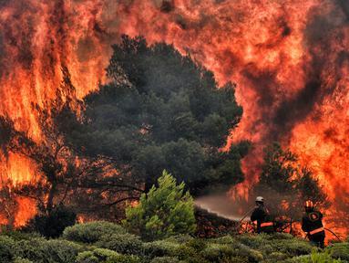 Petugas pemadam kebakaran mencoba memadamkan api saat kebakaran di Desa Kineta, dekat Athena, Rabu (24/7). Kebakaran hutan hebat telah menewaskan 74 orang di Yunani. (AFP Photo/Valerie Gache)