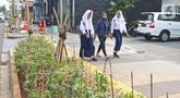 Pelajar melintasi trotoar di kawasan Kemang, Jakarta, Selasa (15/10/2019). Pemerintah Provinsi DKI menargetkan pelebaran dan penataan trotoar ini akan rampung pada Desember 2019. (Liputan6.com/Herman Zakharia)