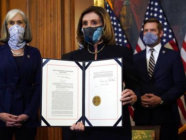Ketua DPR Nancy Pelosi menampilkan dokumen pemakzulan Presiden Donald Trump yang ditandatanganinya di Capitol Hill, Washington, Amerika Serikat, Rabu (13/1/2021). Jelang akhir kekuasaannya, Donald Trump kembali dimakzulkan oleh DPR AS untuk kedua kalinya. (AP Photo/Alex Brandon)