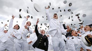"""Lulusan US Naval Academy melemparkan topinya ke udara usai upacara kelulusan di Annapolis, Maryland, (26/5). Akademi ini didirikan 10 Oktober 1845, dan sering hanya disebut """"Anapolis"""". (AP Photo / Patrick Semansky)"""