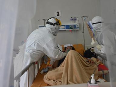 Petugas medis memeriksa pasien COVID-19 di rumah sakit umum di Bogor, Jawa Barat, Senin (25/1/2021). Angka kasus COVID-19 di Kota Bogor pada masa pemberlakuan pembatasan kegiatan masyarakat (PPKM) terus meningkat. (ADEK BERRY/AFP)