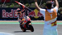Pembalap Repsol Honda, Marc Marquez membawa bendera saat berselebrasi usai memenangi balapan MotoGP Spanyol 2018 di Sirkuit Jerez, Minggu (6/5). Marquez mengukir waktu 41 menit 39,678 detik. (AFP Photo/ JAVIER SORIANO)