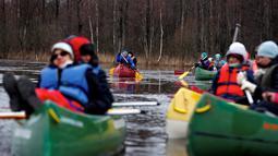 Pengunjung mendayung kayak di tengah banjir yang merendam padang rumput Taman Nasional Soomaa, Estonia, Minggu (17/3). Wisata banjir ini, menjadi daya tarik tersendiri bagi pengunjung. (Reuters/Ints Kalnins)