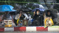 Pelayat menggunakan payung sambil menunggu hujan demi menghadiri upacara kremasi Raja Thailand Bhumibol Adulyadej di Bangkok, Selasa (24/10). Prosesi kremasi Raja Bhumibol dilaporkan telah menelan biaya hingga sekitar Rp1,2 triliun. (AP/Wason Wanichakorn)