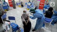 Petugas kesehatan menyuntikkan vaksin COVID-19 kepada guru di dalam ruang kelas SDIT Al Muhajirin, Depok, Selasa (18/5/2021). Sebanyak 2.000 guru di wilayah Depok divaksinasi dalam rangka persiapan kegiatan pembelajaran tatap muka pada tahun ajaran baru Juli mendatang. (merdeka.com/Arie Basuki)
