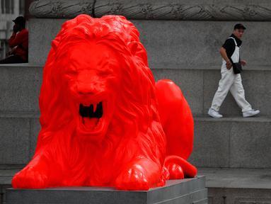 Wisatawan berjalan di dekat singa fluorescent merah yang bergabung dengan empat singa tradisional lainnya di Trafalgar Square di London (19/9). Patung Singa merah tersebut dipajang sebagai bagian dari Festival Desain London. (AP Photo/Frank Augstein)