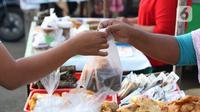 Warga melakukan aktivitas jual beli makanan untuk berbuka puasa (takjil) di kawasan Jalan Panjang, Jakarta, Selasa (5/5/2020). Pandemi virus COVID-19 dan pelaksanaan Pembatasan Sosial Berskala Besar (PSBB) berimbas pada sepinya pembeli takjil di kawasan tersebut. (Liputan6.com/Helmi Fithriansyah)