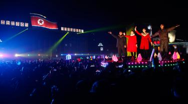 Artis Korea Utara menyapa warga saat pertunjukan Tahun Baru 2019 di Kim Il Sung Square, Pyongyang, Selasa (1/1). Grup seni hingga opera memeriahkan perayaan Tahun Baru 2019 di Korea Utara. (AP Photo/Jon Chol Jin)