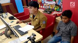 Petugas Disdukcapil Kota Tangerang Selatan melakukan pembuatan Kartu Identitas Anak (KIA) di tempat makan siap saji kawasan Bintaro Tangerang Selatan, Selasa (26/2). (Merdeka.com/Arie Basuki)