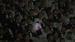 Pengantin wanita bermain smartphone-nya dalam upacara pernikahan massal di Cheong Shim Peace World Center, Gapyeong, Korea Selatan, Jumat, (7/2/2020). Wabah virus corona yang melanda sejumlah wilayah di dunia tidak menghalangi antusias warga Korsel mengikuti acara itu. (AP Photo/Ahn Young-joon)