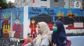 Pengendara motor melintas di depan mural bertema Kota Jakarta di sekitar Rusunawa KS Tubun, Jakarta, Senin (23/11/2020). Mural tersebut dibuat guna memercantik lingkungan di sekitar rusun agar lebih berwarna dan tidak tampak kumuh. (Liputan6.com/Immanuel Antonius)