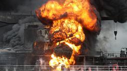 Api melahap kapal kargo di pelabuhan Ulsan, di pantai tenggara Korea Selatan (28/9/2019). Menurut pihak berwenang, sembilan pelaut terluka setelah kebakaran terjadi di kapal kargo dan menyebar ke kapal lain menyusul ledakan di kota pelabuhan tenggara Ulsan tersebut. (AFP/Yonhap)