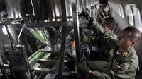 Anggota TNI AU memasang tabung penampung garam di dalam pesawat CN-295 selama perasi Teknologi Modifikasi Cuaca (TMC) di Lanud Halim Perdanakusuma, Jakarta, Kamis (9/1/2020). (merdeka.com/Iqbal S. Nugroho)