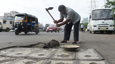 Foto pada 29 Agustus 2018, Dadarao Bilhore (48) menutup jalan yang berlubang di jalan raya Western Express, Mumbai. Ayah asal India itu mengobati kesedihannya dengan menutupi lubang di jalan raya serta meratakan jalanan yang rusa. (INDRANIL MUKHERJEE/AFP)