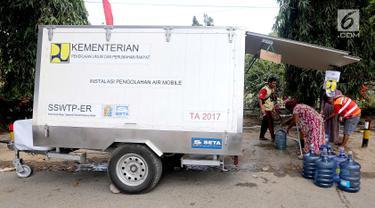 Sebuah mobil instalasi pengolahan air Kementerian PUPR mendistribusikan air untuk kebutuhan pengungsi korban gempa dan tsunami Palu di halaman kantor Wali Kota Palu, Sulawesi Tengah, Senin (8/10). (Liputan6.com/Fery Pradolo)