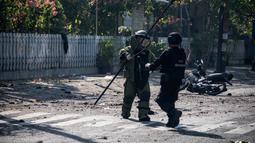 Petugas Gegana Brimob Jawa Timur menyisir lokasi ledakan bom di sekitar gereja di Surabaya, Minggu (13/5). Ledakan terjadi di tiga gereja, yakni Santa Maria di Ngagel, GKI di Jalan Diponegoro dan dan sebuah gereja di Jalan Arjuna. (AFP/JUNI KRISWANTO)