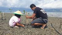Seorang warga bersama putrinya menanam mangrove di pesisir Kelurahan Panau, Kota Palu, Sabtu (10/4/2021). Aksi tersebut selain sebagai upaya mitigasi dari bencana juga diharapkan meningkatkan hasil tangkap nelayan setempat. (Foto: Dokumentasi KIARA).