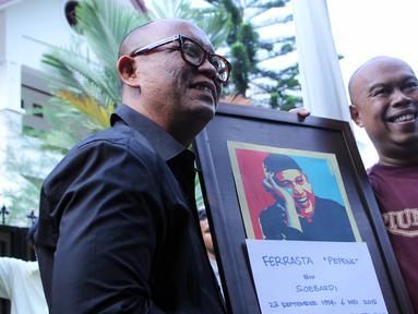 Pembawa acara dan penyanyi, Teuku Edwin dan Jody Sumantri memegang foto almarhum Ferrasta Soebardi alias Pepeng di rumah duka di kawasan Cinere, Depok, Rabu (6/5/2015). Pepeng meninggal dunia di usia 60 tahun. (Liputan6.com/Helmi Afandi)