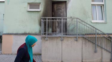 Seorang wanita berhijab melintas di pintu Masjid Fatih Camii yang rusak akibat serangan bom di Dresden, Jerman Timur, Senin (26/9) malam. Tidak ada korban namun terdapat kerusakan di bangunan masjid akibat getaran ledakan itu. (SEBASTIAN KAHNERT/DPA/AFP)