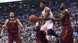 Pemain Raptors, Kyle Lowry (tengah) berusaha melewati adangan dua pemain Cleveland pada laga NBA basketball playoffs Eastern Conference semifinal di Air Canada Centre, (1/2/2018). Cavaliers menang 113-112. (Nathan Denette/The Canadian Press via AP)