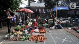 Pedagang berjualan dekat tanda 'X' yang digunakan sebagai pembatas physical distancing di Pasar Perumnas Klender, Jakarta, Kamis (18/6/2020). Selain sistem ganjil genap kios, pengelola pasar menerapkan physical distancing antarlapak untuk mencegah penularan COVID-19. (merdeka.com/Iqbal S. Nugroho)