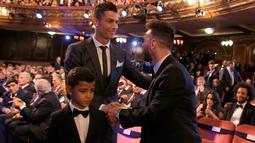 Bintang Real Madrid Cristiano Ronaldo mendapat ucapan selamat dari bintang Argentina, Lionel Messi usai meraih pemain terbaik pada acara The Best FIFA Football Awards 2017 di London, Senin (23/10). Ronaldo mengalahkan Messi dan Neymar. (AP/Alastair Grant)