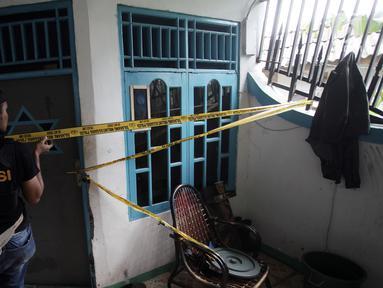 Petugas memasang garis polisi di sebuah rumah seusai penggerebekan peredaran narkoba di kawasan Kampung Ambon, Cengkarang, Jakarta, Rabu (24/1). Dalam penggrebekan, dikerahkan sekitar 150 personel gabungan dari Brimob dan TNI. (Liputan6.com/Arya Manggala)