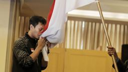 Atlet Bulutangkis Indonesia, Mohammad Ahsan, mencium bendera saat acara pelepasan di Hotel Atlet Century, Senayan, Selasa (8/5/2018). Acara pelepasan tersebut sekaligus merayakan ulang tahun PBSI ke 67. (Bola.com/M Iqbal Ichsan)