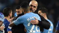 Pelatih Manchester City, Pep Guardiola, memeluk Riyad Mahrez, usai mengalahkan Chelsea pada laga Premier League di Stadion Etihad, Manchester, Sabtu (23/11). City menang 2-1 atas Chelsea. (AFP/Oli Scarff)