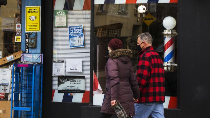 Sejumlah orang yang mengenakan masker berjalan melewati tempat pangkas rambut yang tutup di Toronto, Kanada, 23 November 2020. Kanada telah mengonfirmasi total 337.555 kasus COVID-19 dan 11.521 kematian. (Xinhua/Zou Zheng)