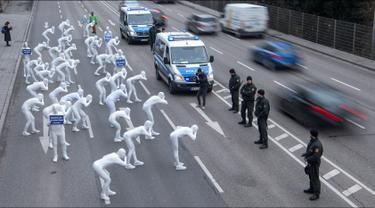 Aktivis dari Greenpeace mengenakan pakaian serba putih turun ke jalan melakukan aksi di Stuttgart, Jerman (19/2). Mereka melakukan aksi memprotes polusi yang diakibatkan oleh knalpot mobil diesel. (Sebastian Gollnow/dpa/AFP)