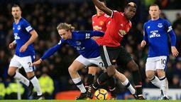 Pemain Everton Tom Davies berebut bola dengan gelandang Manchester United, Paul Pogba saat pertandingan Liga Inggris di Goodison Park, Liverpool (1/1). (Peter Byrne / PA via AP)