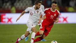 Gelandang Portugal, Bernardo Silva, berebut bola dengan gelandang Serbia, Filip Kostic, pada laga Kualifikasi Piala Eropa 2020 di Belgrade, Sabtu (7/9). Serbia kalah 2-4 dari Portugal. (AFP/Pedja Milosavljevic)