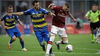 Penyerang AC Milan, Ante Rebic membawa bola dari kawalan pemain Parma, Matteo Darmian pada pertandingan lanjutan Liga Serie A Italia di Stadion San Siro di Milan, Italia (15/7/2020). AC Milan menang telak 3-1 atas Parma. (AP Photo/Luca Bruno)