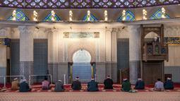 Petugas masjid mendengarkan khotbah salat Jumat dengan menerapkan jaga jarak aman saat Ramadan di Masjid Negara Malaysia, Kuala Lumpur, Malaysia, Jumat (15/5/2020). Masjid Negara Malaysia kembali dibuka setelah pemerintah setempat melonggarkan lockdown akibat pandemi COVID-19. (Mohd RASFAN/AFP)