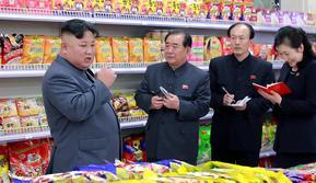 Pemimpin Korea Utara, Kim Jong-un berbincang dengan stafnya ketika berada di toko makanan saat mengunjungi Taesong Department Store setelah dibuka untuk umum di Korea Utara (8/4). (KCNA VIA AFP Photo)